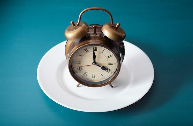 Konzept des intermittierenden fastens, der ketogenen ernährung, des gewichtsverlusts. wecker auf teller