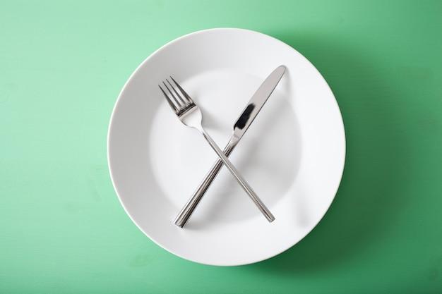 Konzept des intermittierenden fastens und der ketogenen ernährung, gewichtsverlust. gabel und messer auf einem teller gekreuzt