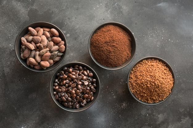 Konzept des kakaos und der kaffeebohnen in den schüsseln auf dunkelheit.