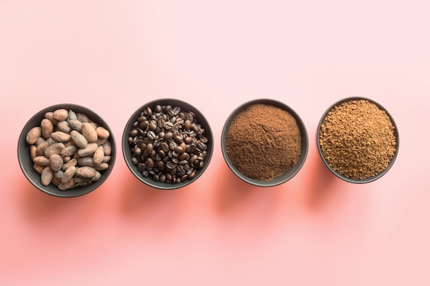 Konzept des kakaos und der kaffeebohnen in den schüsseln auf rosa hintergrund.