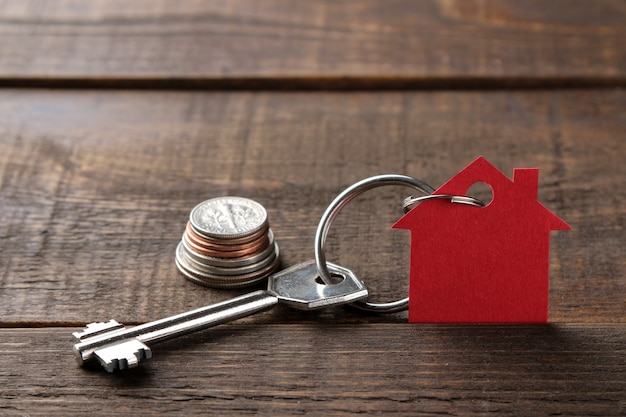 Konzept des kaufs eines hauses. schlüssel mit einem schlüsselbundhaus und geld auf einem braunen hölzernen hintergrund. mit platz für inschrift