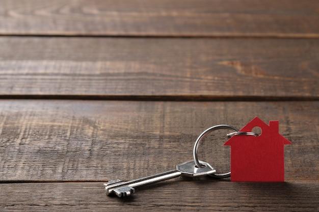 Konzept des kaufs eines hauses. schlüssel mit schlüsselbundhaus auf einem braunen hölzernen hintergrund. mit platz für inschrift
