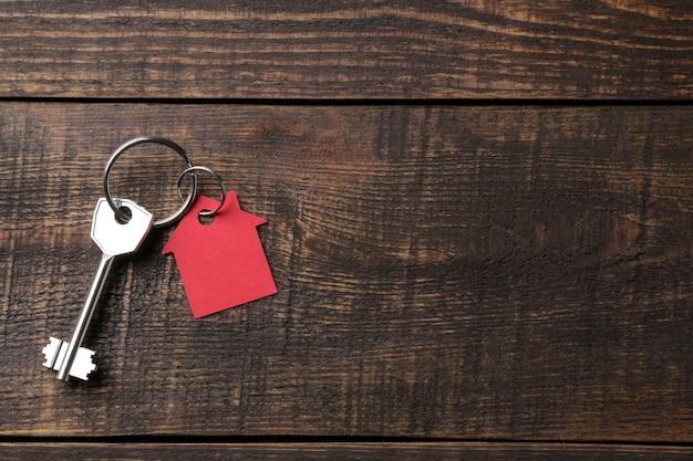 Konzept des kaufs eines hauses. schlüssel mit schlüsselbundhaus auf einem braunen hölzernen hintergrund. von oben betrachten. mit platz für inschrift