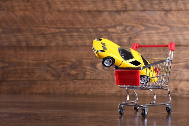 Konzept des kaufs eines neuen autos. spielzeugauto im einkaufskorb auf holztisch