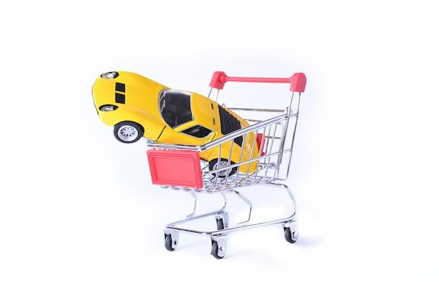 Konzept des kaufs eines neuen autos. spielzeugauto im einkaufskorb isoliert