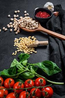 Konzept des kochens von humus. zutaten: knoblauch, kichererbsen, pinienkerne, basilikum, pfeffer. schwarzer hintergrund. ansicht von oben.
