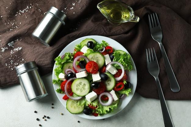 Konzept des köstlichen essens mit griechischem salat auf weißem strukturiertem hintergrund