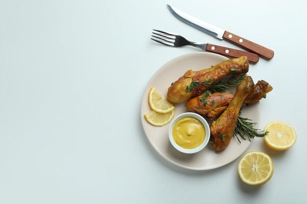 Konzept des köstlichen essens mit platte von brathähnchen-trommelstöcken auf weißem hintergrund
