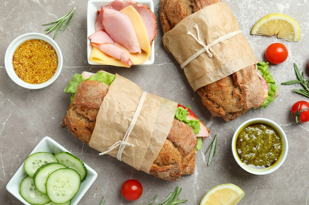 Konzept des leckeren essens mit ciabatta-sandwiches auf grauem strukturiertem tisch