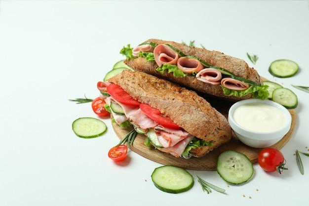 Konzept des leckeren essens mit ciabatta-sandwiches auf weißem hintergrund