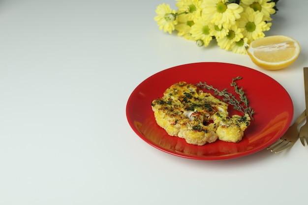 Konzept des leckeren essens mit gebackenem blumenkohl auf weißem hintergrund..