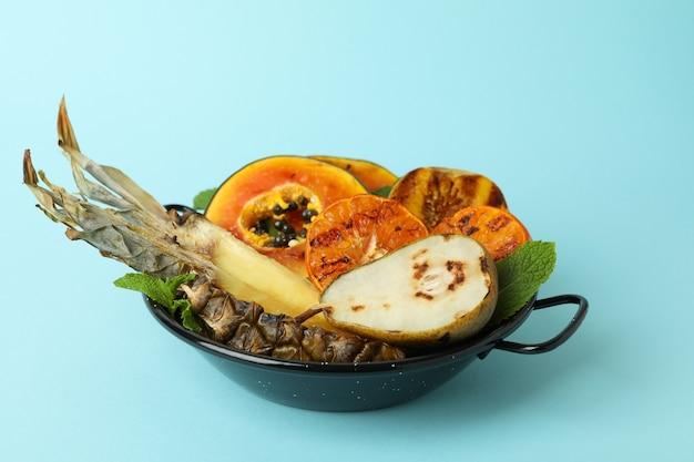 Konzept des leckeren essens mit gegrillten früchten auf blauem hintergrund.