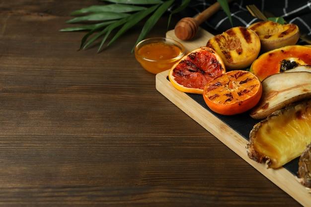 Konzept des leckeren essens mit gegrillten früchten auf holzhintergrund.