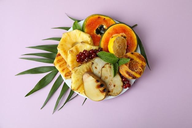 Konzept des leckeren essens mit gegrillten früchten auf violettem hintergrund.