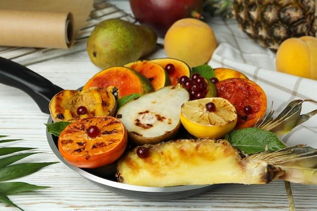 Konzept des leckeren essens mit gegrillten früchten auf weißem holztisch.