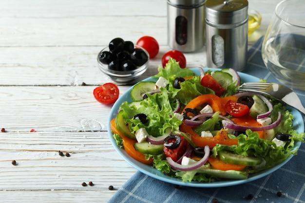 Konzept des leckeren essens mit griechischem salat auf weißem holztisch
