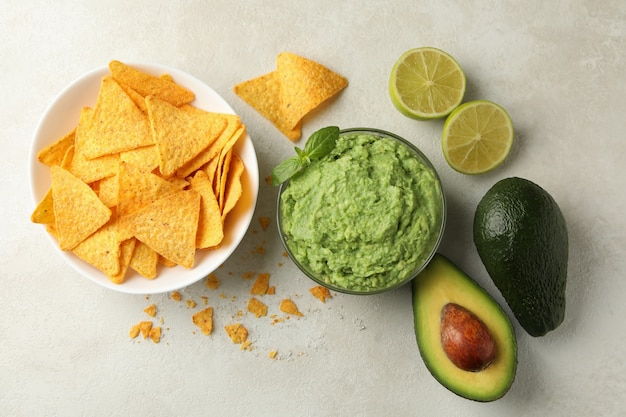 Konzept des leckeren essens mit guacamole und chips auf weißem strukturiertem hintergrund, draufsicht