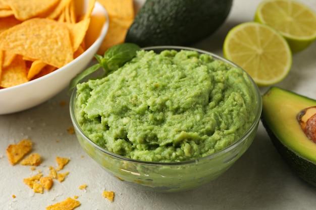 Konzept des leckeren essens mit guacamole und chips auf weißem strukturiertem hintergrund, nahaufnahme