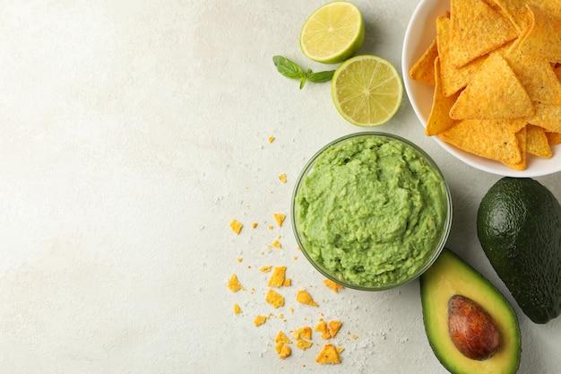 Konzept des leckeren essens mit guacamole und chips auf weißem strukturiertem hintergrund, raum für text
