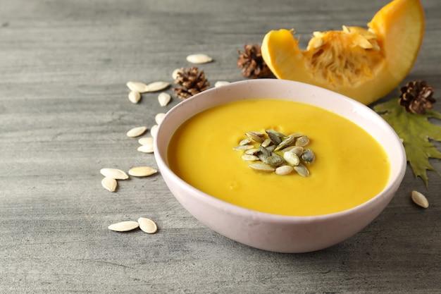 Konzept des leckeren essens mit kürbissuppe auf grauem strukturiertem tisch