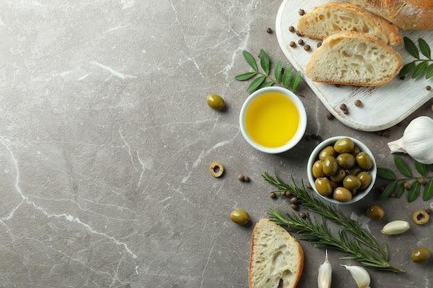Konzept des leckeren essens mit olivenöl auf grau strukturiertem tisch
