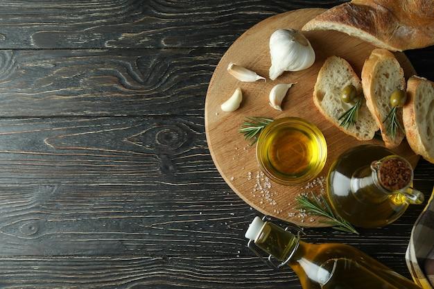 Konzept des leckeren essens mit schüssel olivenöl auf holztisch