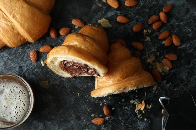 Konzept des leckeren frühstücks mit croissant mit schokolade auf dunkelheit Premium Fotos