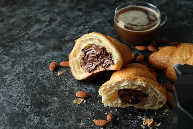 Konzept des leckeren frühstücks mit croissant mit schokolade auf dunkelheit