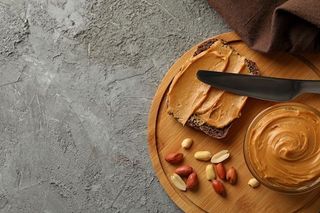 Konzept des leckeren frühstücks mit erdnuss und erdnussbutter auf grauem tisch