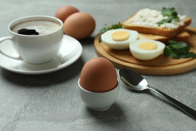 Konzept des leckeren frühstücks mit gekochten eiern auf grauem strukturiertem tisch