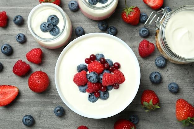 Konzept des leckeren frühstücks mit joghurt auf grauem strukturiertem tisch