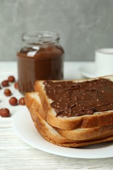 Konzept des leckeren frühstücks mit schokoladenpaste auf weißem holztisch