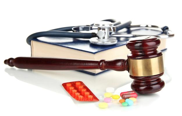 Konzept des medizinrechts. hammer und pillen isoliert auf weiss