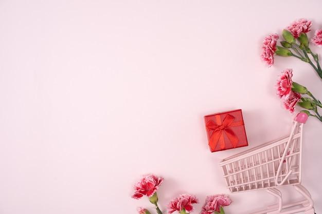 Konzept des muttertagsfeiertagsgrußentwurfs mit nelkenstrauß und geschenk auf rosa hintergrund