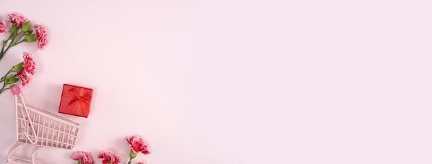 Konzept des muttertagsfeiertagsgrußentwurfs mit nelkenstrauß und geschenk auf rosa oberfläche