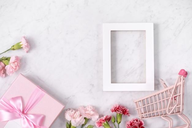 Konzept des muttertagsfeiertagsgrußentwurfs mit nelkenstrauß und geschenk auf weißem marmorhintergrund