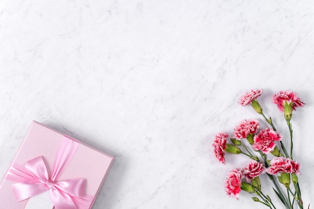 Konzept des muttertagsfeiertagsgrußgeschenkentwurfs mit nelkenstrauß auf weißem marmorhintergrund