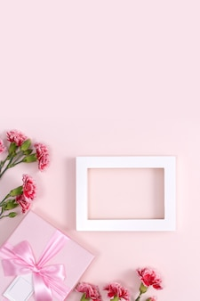 Konzept des muttertagsfeiertagsgrußhintergrunddesigns mit nelkenstrauß auf rosa hintergrund