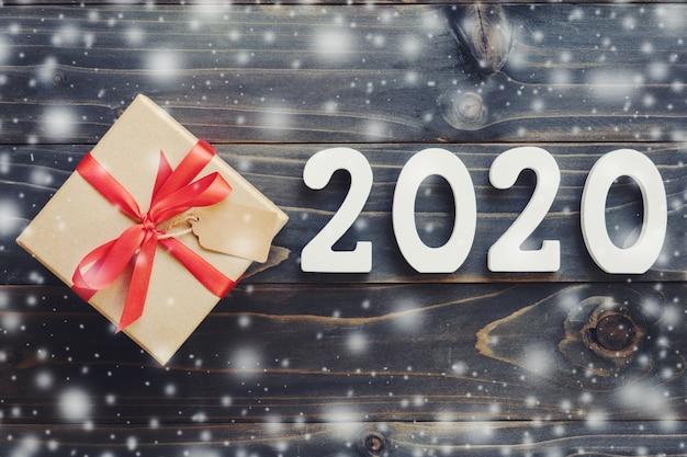 Konzept des neuen jahres 2020: 2020 hölzerne zahl und braune geschenkbox mit schnee auf hölzernem tabellenhintergrund.
