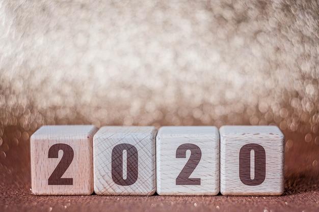 Konzept des neuen jahres 2020 mit hölzernen würfeln auf goldenem hintergrund