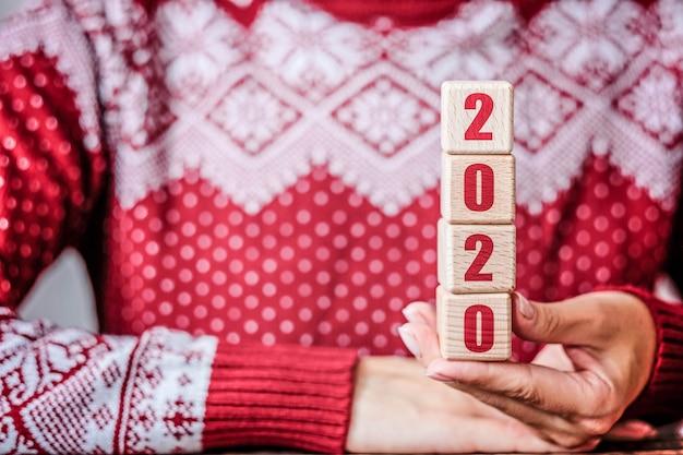 Konzept des neuen jahres 2020 mit hölzernen würfeln in den händen der frau