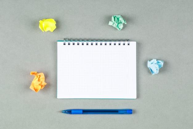 Konzept des notierens mit stift, notizbuch, zerrissenen notizen auf grauer hintergrundoberansicht. platz für horizontales textbild