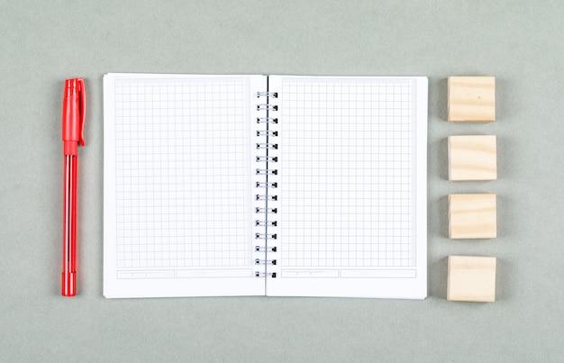 Konzept des offenen notizbuchs und der notiz. mit stift, holzklötze auf grauer hintergrundansicht von oben. platz für horizontales textbild