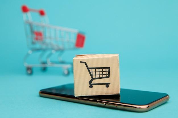 Konzept des online-shoppings. box und einkaufstasche über smartphone auf blau