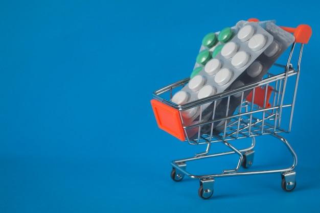 Konzept des online-shoppings, der bestellung und lieferung von medikamenten. blisterpackungen mit medikamenten in einem einkaufswagen auf blauem hintergrund