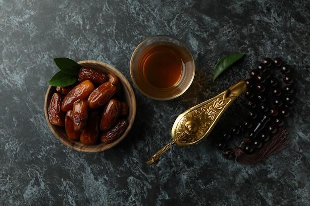 Konzept des ramadan mit lebensmitteln und accessoires auf schwarzer rauchiger oberfläche