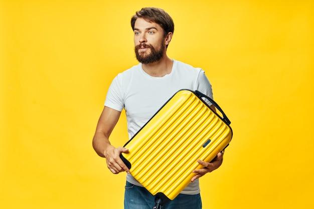 Konzept des reisepassagiers mit mann und gelbem koffer
