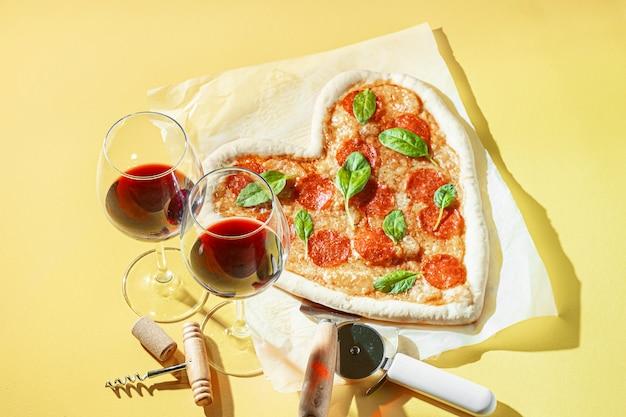 Konzept des romantischen abendessens für zwei mit rotwein und pizza in form eines herzens. abendessen zum valentinstag