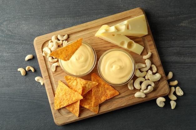 Konzept des snacks mit käsesauce auf dunklem holztisch, ansicht von oben