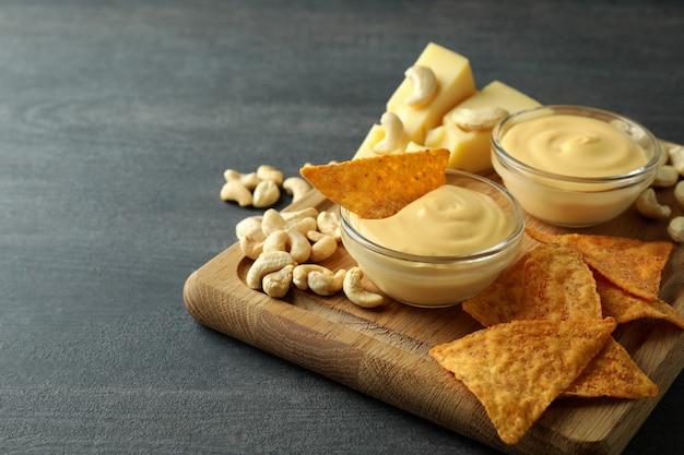 Konzept des snacks mit käsesauce auf dunklem holztisch